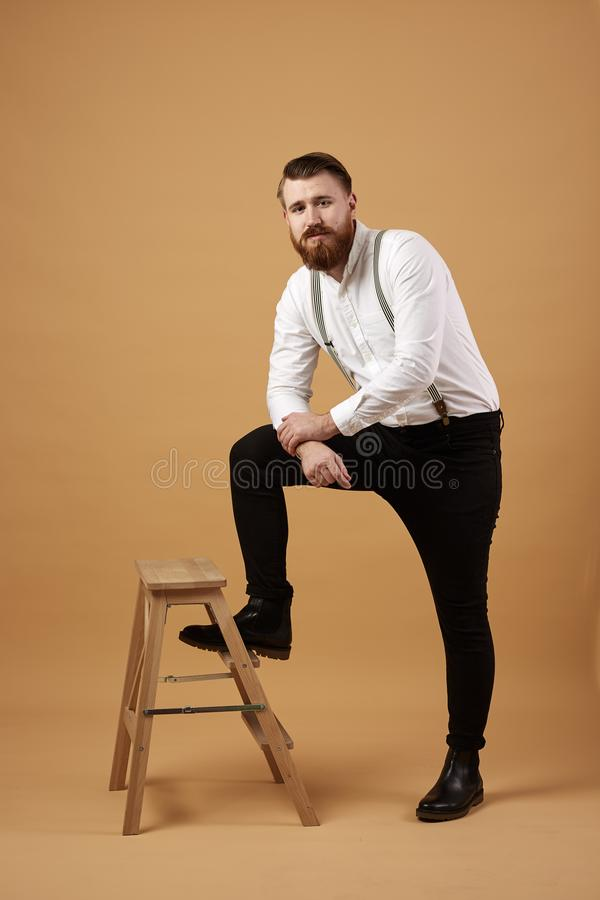 Stylish red-haired man with beard dressed in a white shirt and black trousers with suspender stands next to a wooden stock photography