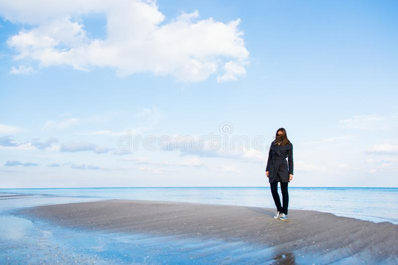 Stylish red-haired woman in dark coat and sunglasses standing on seaside with beautiful sky and water on background royalty free stock image