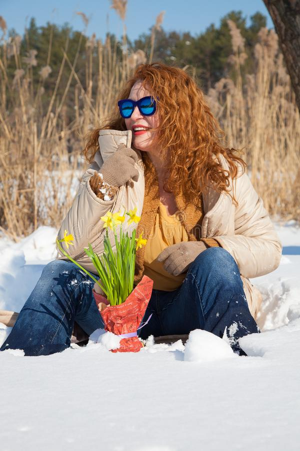 Stylish red haired woman looking away while sitting on snow surface royalty free stock image