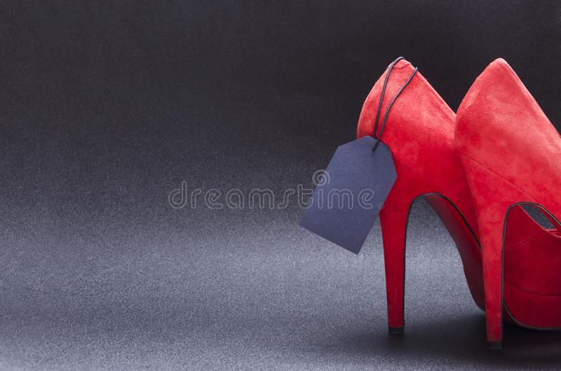 Stylish red high heels and black price tag on the dark background.Concept of black friday and sale stock photo