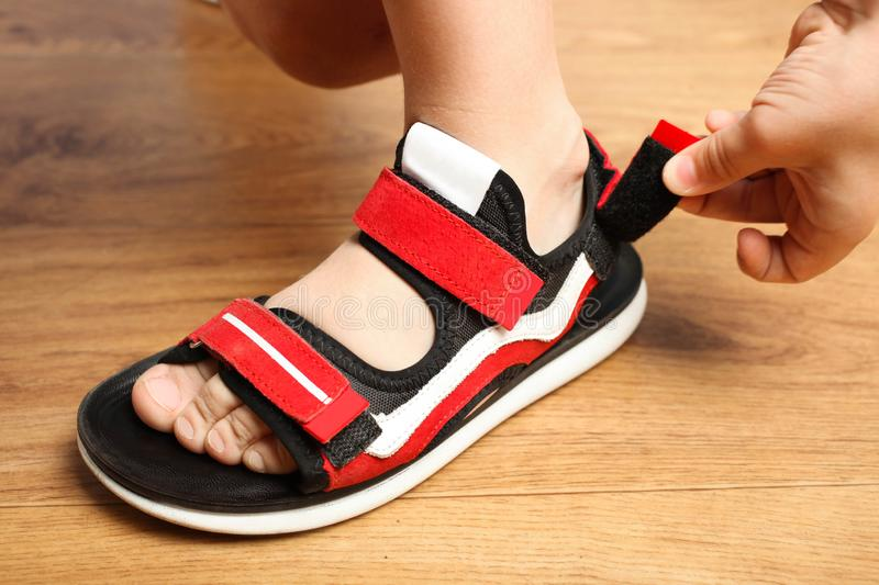 Stylish red sandals with velcro. On foot of boy on wooden background. Concept summer shoes. Clothe-up royalty free stock photo