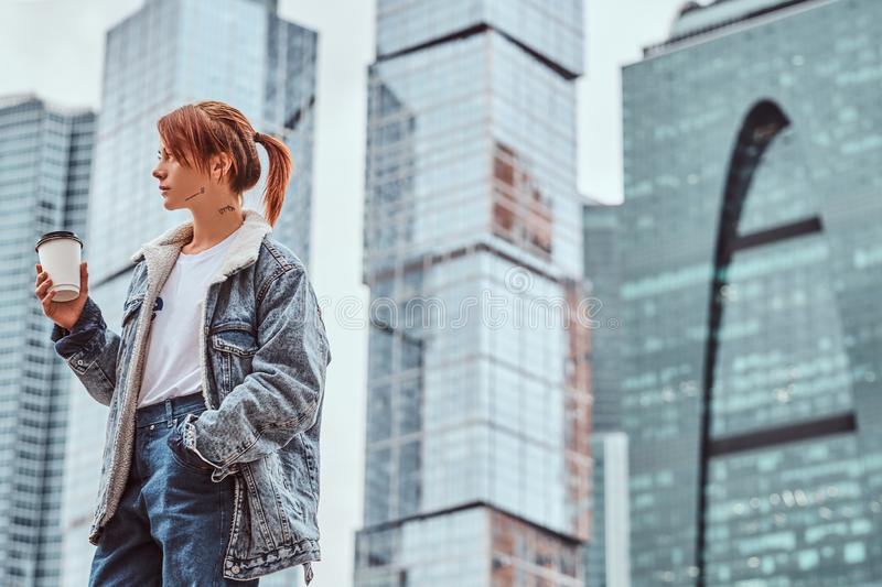 Stylish redhead hipster girl with tattoo on her face wearing denim jacket holding takeaway coffee in front of royalty free stock images