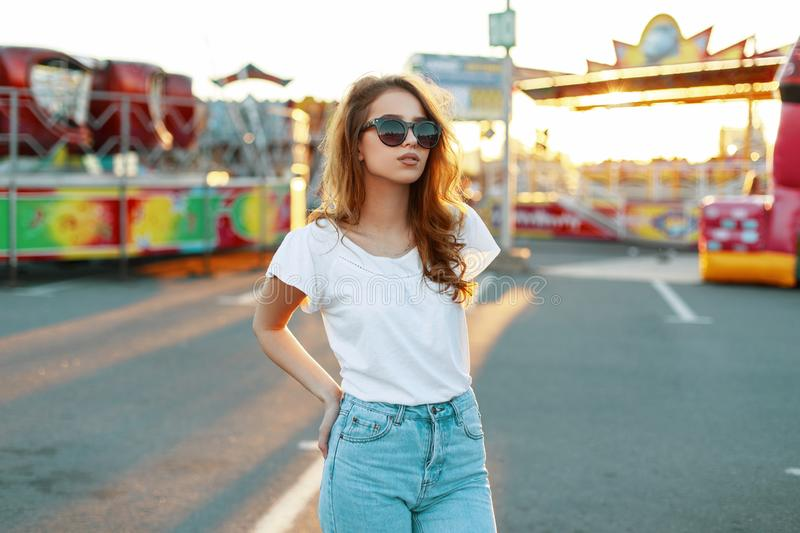 Stylish redhead modern hipster young woman in trendy sunglasses in a white t-shirt in vintage jeans posing royalty free stock photography