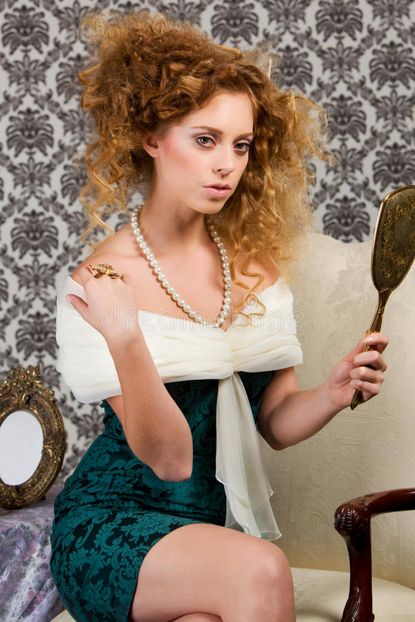 Stylish redheaded model with antique mirror. Redheaded model sitting in antique chair wearing a pearl necklace with victorian/vintage green dress holding an royalty free stock image