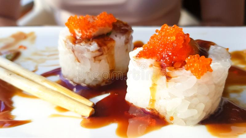 Stylish roll with tempura shrimp in a hot unagi sauce. sushi rolls with chopsticks in sauce on a white plate with food stock photo