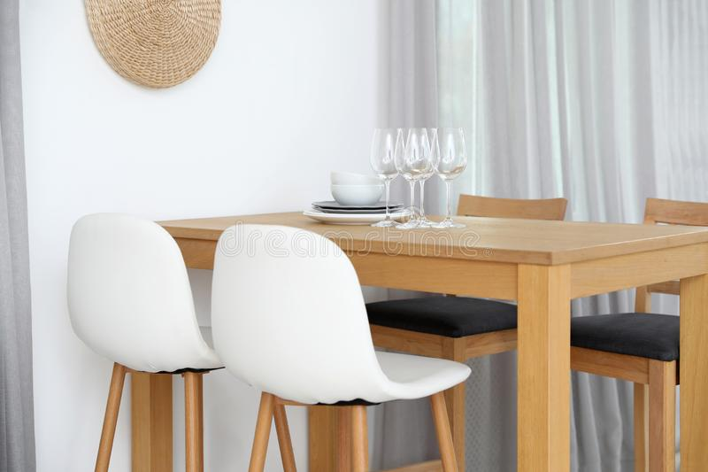 Stylish room interior with dining table and bar stools near wall stock photography