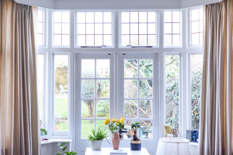 Stylish room interior with french doors and light neutral colours in a modern home. Light and airy room in day time stock images