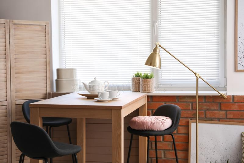 Stylish room interior with modern furniture and window. Blinds stock photo