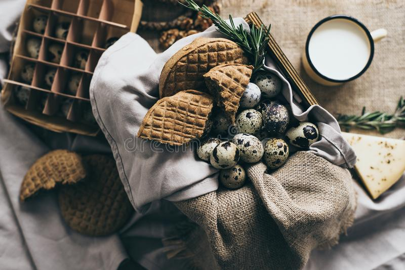 Stylish rustic still life with cheeses and different kinds of bread in beige warm colors with craft napkin used as a stock images