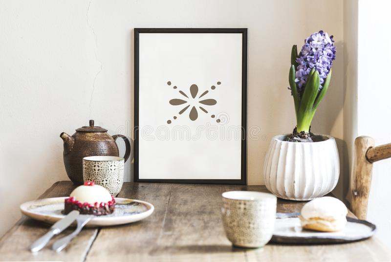Stylish scandi interior design of kitchen space with small table with mock up frame, plant, cups of tea and tasty dessert. royalty free stock images