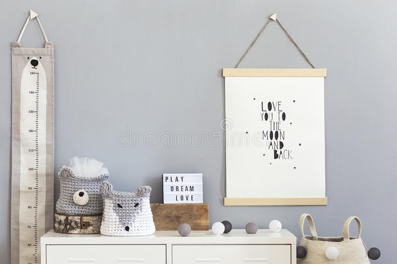 Stylish scandinavian nursery interior with hanging mock up poster, natural toys, teddy bears, children`s accessories and design stock photography