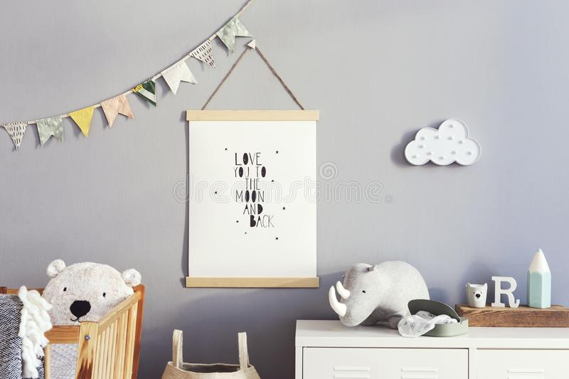 Stylish scandinavian nursery interior with hanging mock up poster, natural toys, teddy bears, children`s accessories and design stock photo