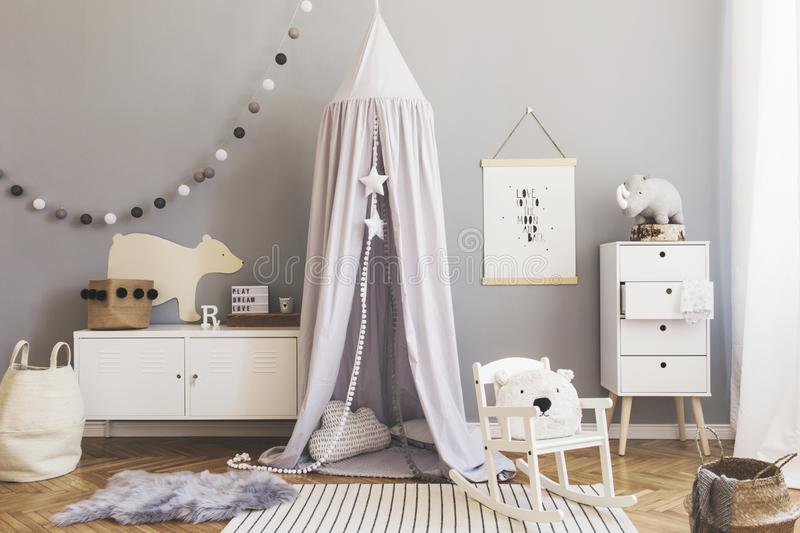 Stylish scandinavian nursery interior with hanging mock up poster, natural toys, teddy bears, children`s accessories and design stock images