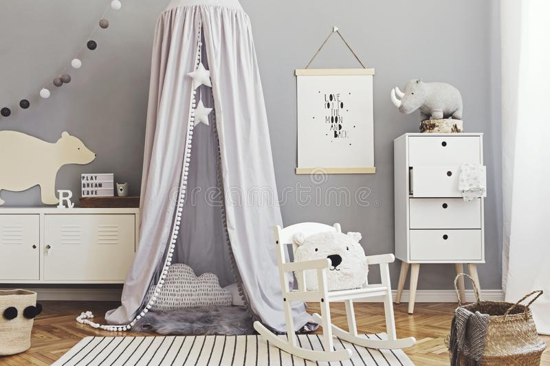 Stylish scandinavian nursery interior with hanging mock up poster, natural toys, teddy bears, children`s accessories and design royalty free stock photos