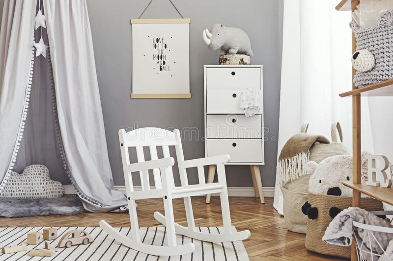 Stylish scandinavian nursery interior with hanging mock up poster, natural toys, teddy bears, children`s accessories and design stock image