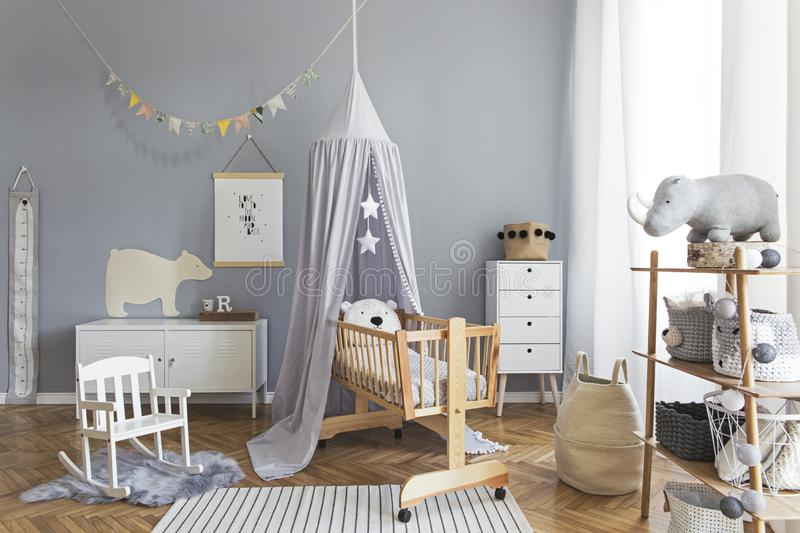 Stylish scandinavian nursery interior with hanging mock up poster, natural toys, teddy bears, children`s accessories and design royalty free stock photography