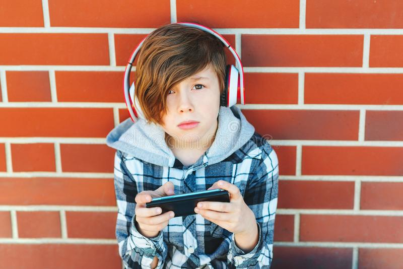 Stylish schoolboy with smartphone and headphones listening to music or playing game over brick wall. Leisure, children, technology. And people concept stock images