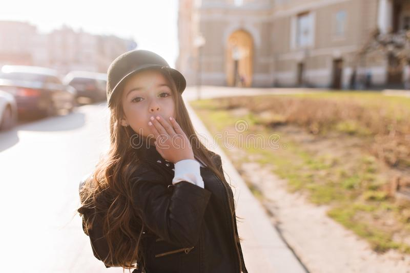 Stylish schoolgirl going home after classes, wearing backpack and trendy black hat. Portrait of surprised little girl royalty free stock photos