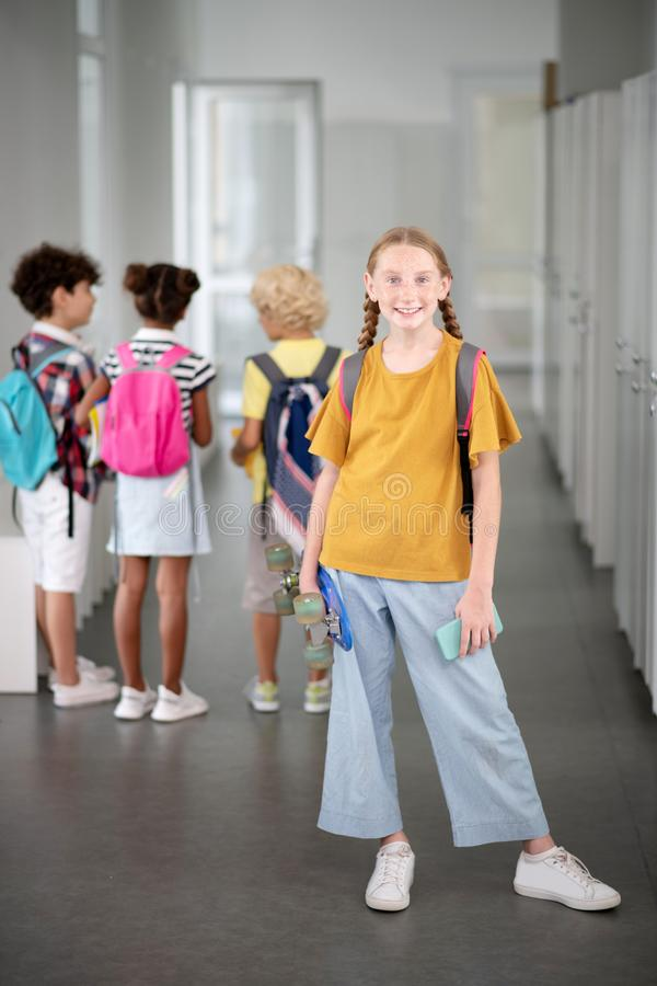 Stylish schoolgirl holding penny board and smartphone stock photos
