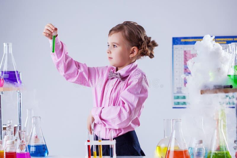 Stylish schoolgirl posing in chemistry lab stock images