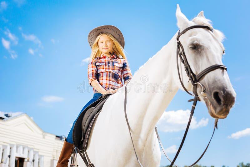 Stylish schoolgirl sitting on white gentle racing horse stock photos