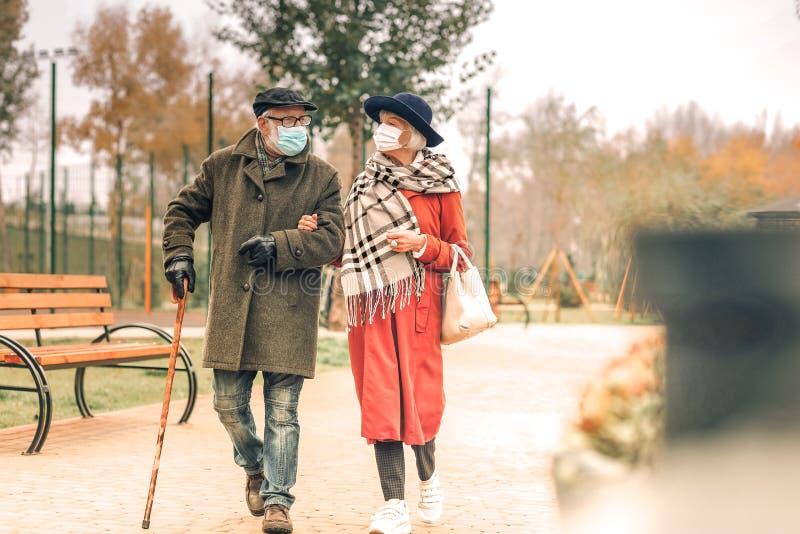 Stylish senior couple wearing face masks walking in park together royalty free stock photos
