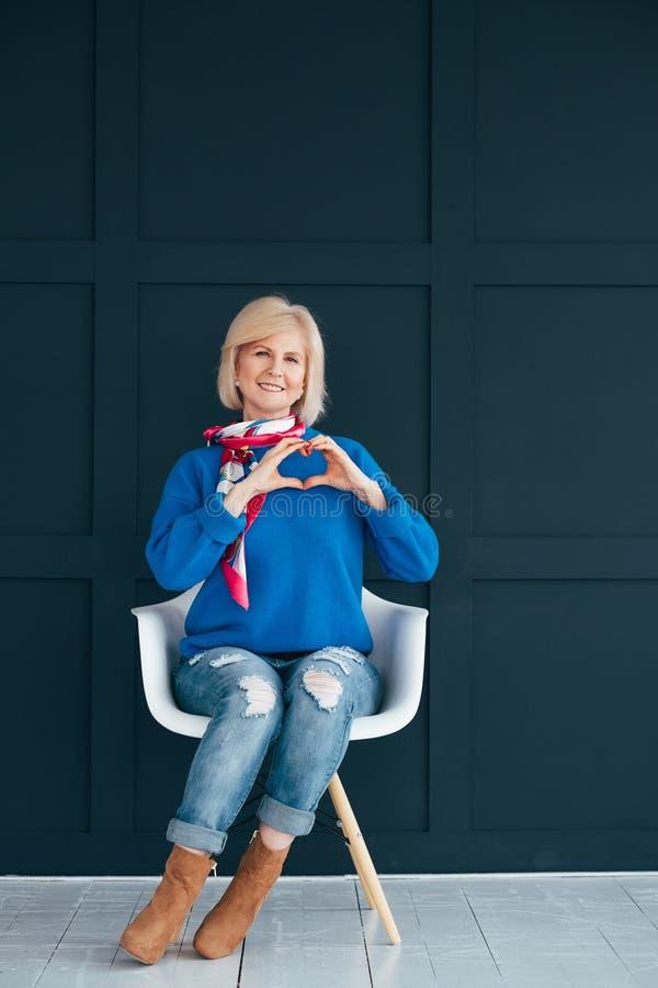 Stylish senior woman heart shape hand care stock photo