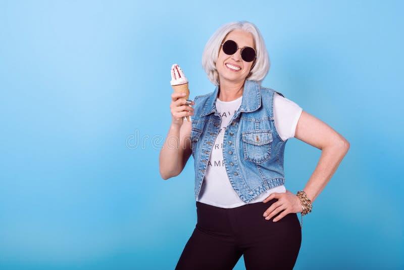 Stylish senior woman holding an icecream and smiling. stock image