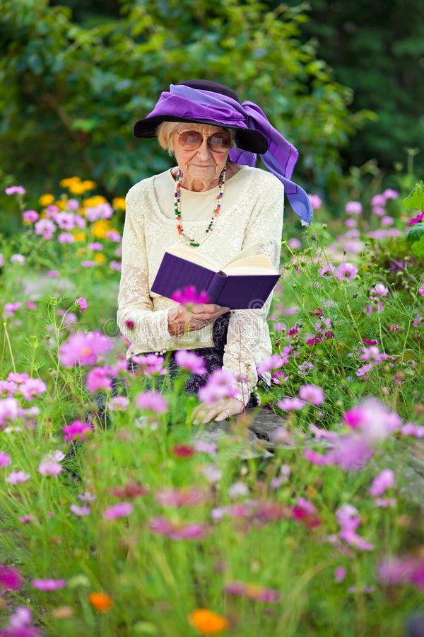 Stylish senior woman reading outdoors royalty free stock photos