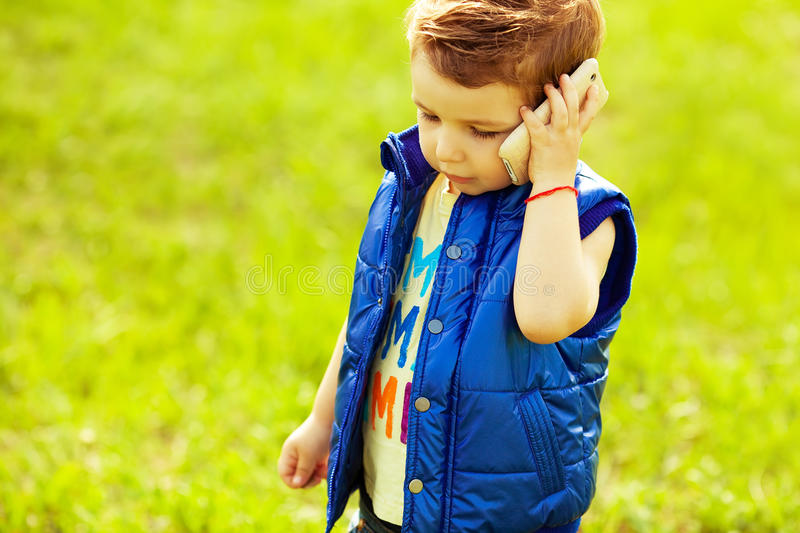 Stylish serious baby boy with ginger (red) using smartphone royalty free stock photography