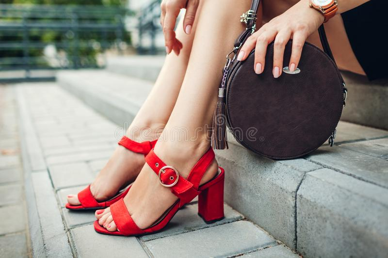 Stylish shoes and accessories. Young woman wearing fashionable red high-heeled sandals and holding handbag. Sitting on stairs outdoors royalty free stock photography