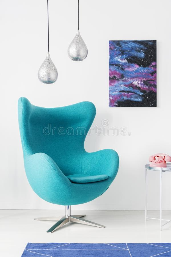 Stylish silver lamps above blue egg chair in modern living room interior with cosmos graphic on the wall, real photo stock image