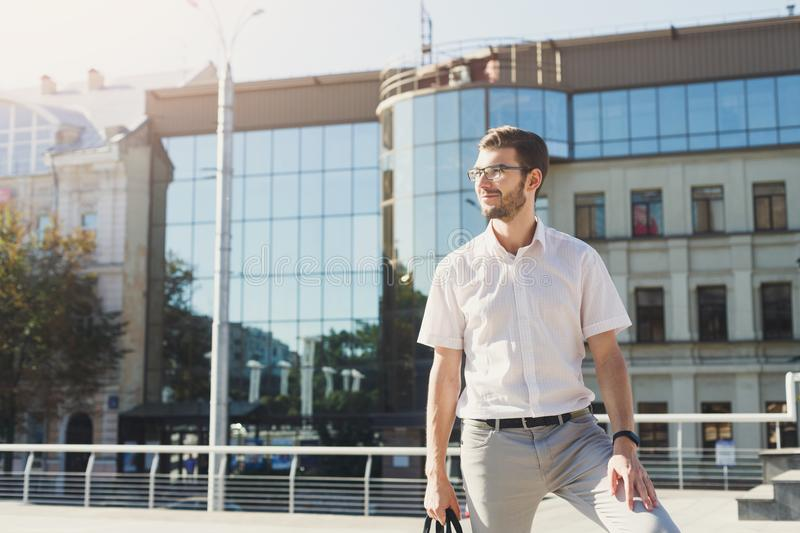Stylish smiling businessman standing outdoors stock photo