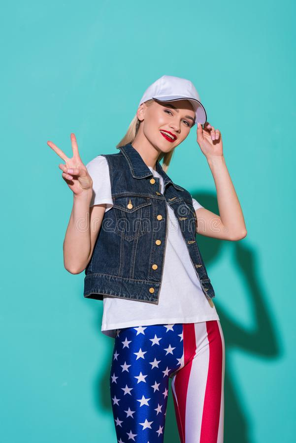 stylish smiling woman in cap, white shirt, denim jacket and leggings with american flag pattern showing peace sign royalty free stock photo