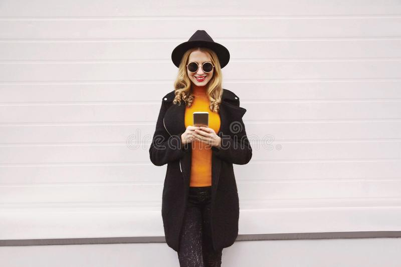 Stylish smiling woman looking at phone wearing black coat jacket, round hat, sunglasses in city on gray wall stock image