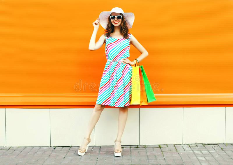 Stylish smiling woman with shopping bags wearing colorful striped dress, summer straw hat posing on orange wall. Background stock images