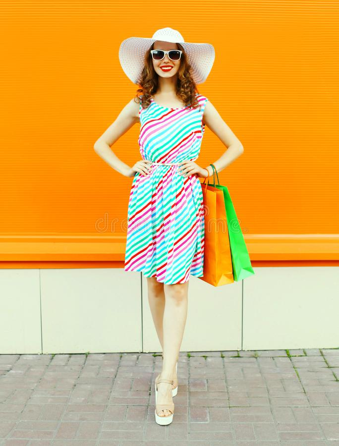 Stylish smiling woman with shopping bags wearing colorful striped dress, summer straw hat posing on orange wall. Background royalty free stock photography