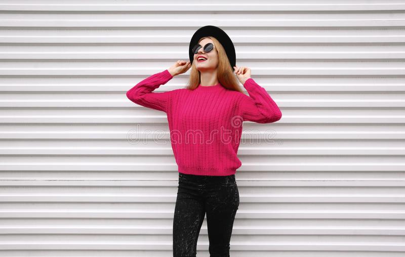 Stylish smiling young girl in colorful pink knitted sweater, black round hat on white wall stock photos