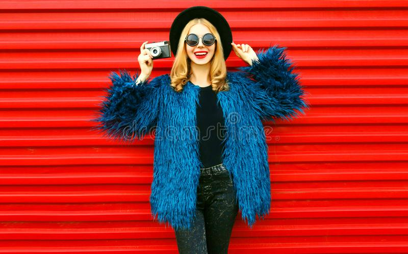 Stylish smiling young woman model with retro camera wearing blue faux fur coat, round hat and sunglasses over red wall royalty free stock photography