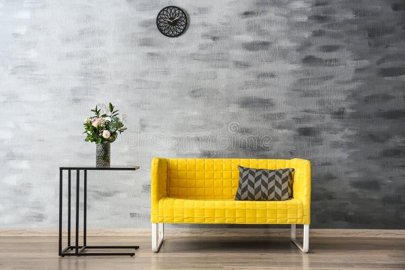 Stylish sofa with table near wall royalty free stock photos