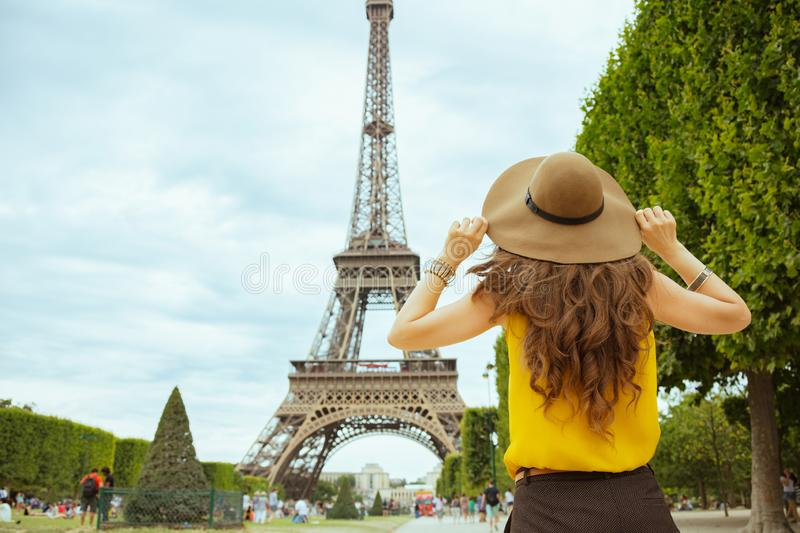 Stylish solo tourist woman in Paris, France sightseeing. Seen from behind stylish solo tourist woman in yellow blouse and hat in Paris, France sightseeing stock image