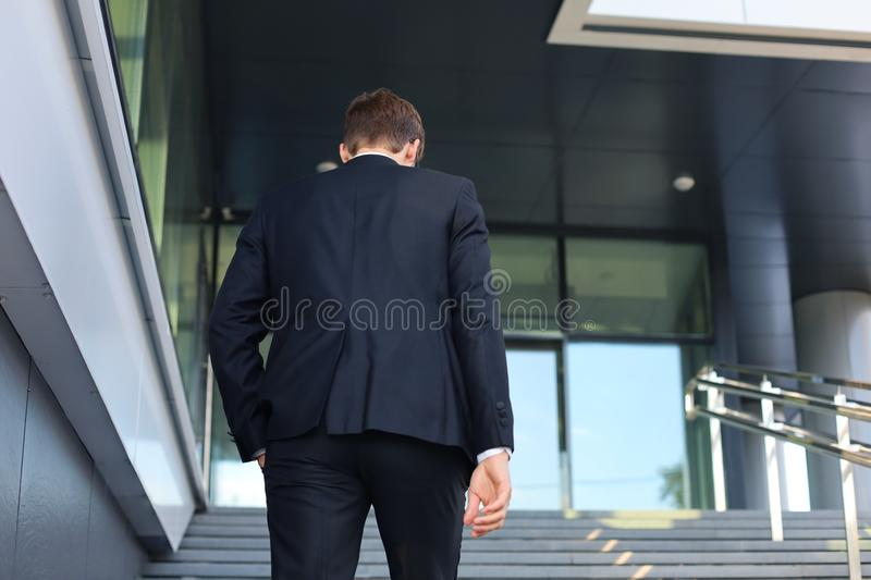 Stylish successful businessman goes up the stairs of the office building.  royalty free stock images