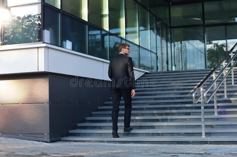 Stylish successful businessman goes up the stairs of the office building.  royalty free stock photography