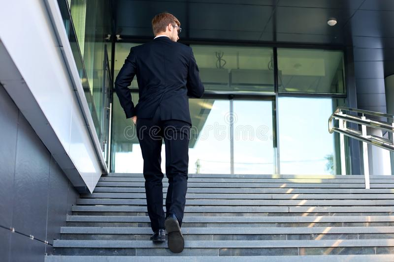 Stylish successful businessman goes up the stairs of the office building.  stock images