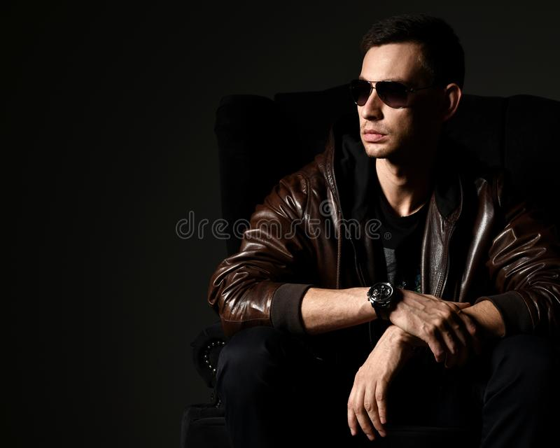 Stylish successful rich man in black t-shirt and brown leather jacket sits and thinks something over. Stylish successful rich man dive in aviator sunglasses royalty free stock images
