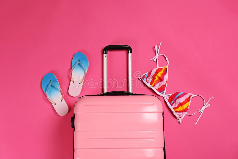 Stylish suitcase, bikini top and flip flops on color background. Top view stock photos