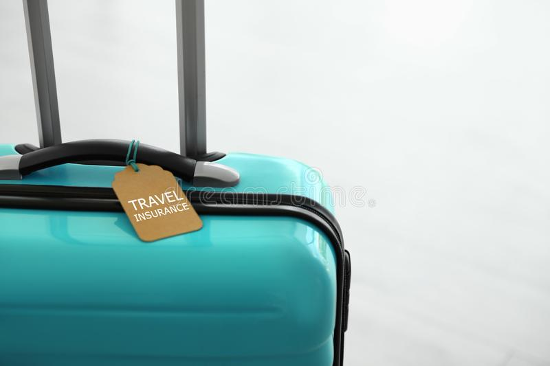 Stylish suitcase with travel insurance label on  background, closeup. Space for text stock photography
