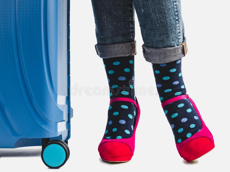 Stylish suitcase, women`s legs, bright socks and pink shoes. On a white, isolated background. Close-up. Concept of style, elegance, beauty and travel stock images