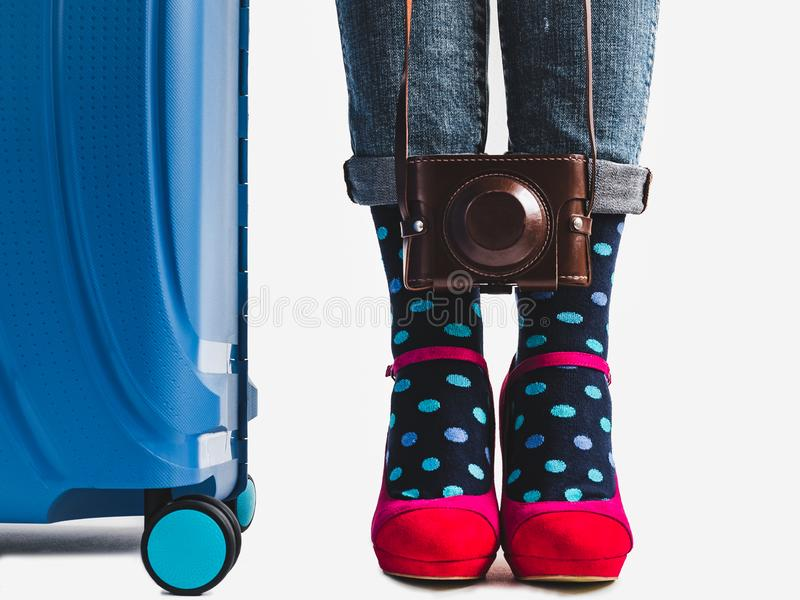 Stylish suitcase, women`s legs and bright socks. Stylish suitcase, women`s legs, bright socks, pink shoes and vintage camera on a white, isolated background stock image