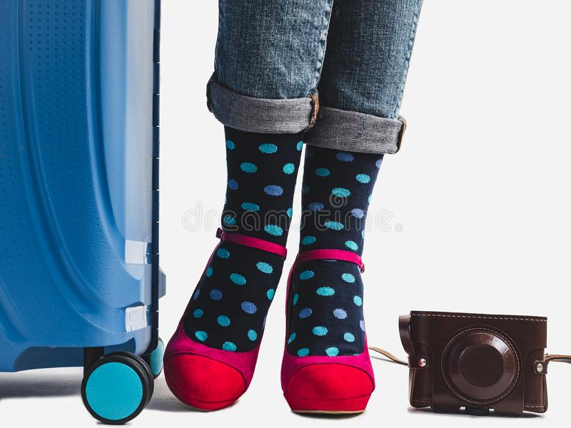 Stylish suitcase, women`s legs and bright socks. Stylish suitcase, women`s legs, bright socks, pink shoes and vintage camera on a white, isolated background royalty free stock photos